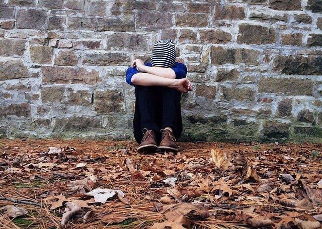 kluk sedí u zdi